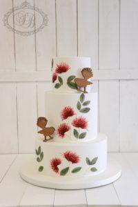 3 tier white wedding cake with pohutukawa flowers