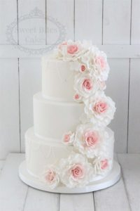 Simple white wedding cake with ombre rose cascade
