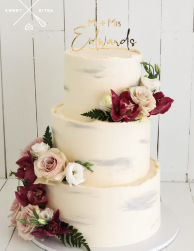 rough edge wedding cake fresh flowers silver brush