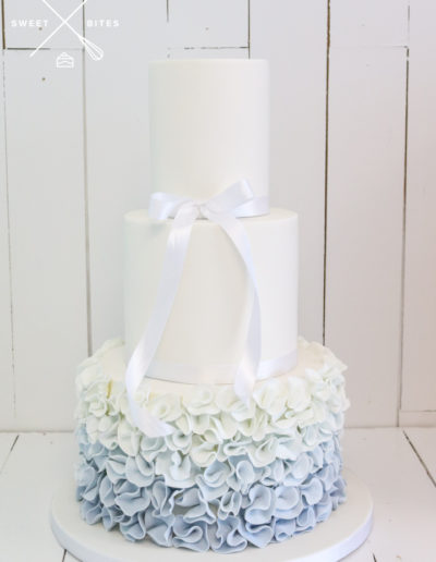blue ombre ruffle wedding cake with bow