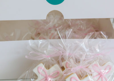individually bagged cross cookies tied ribbon bow white pink fondant